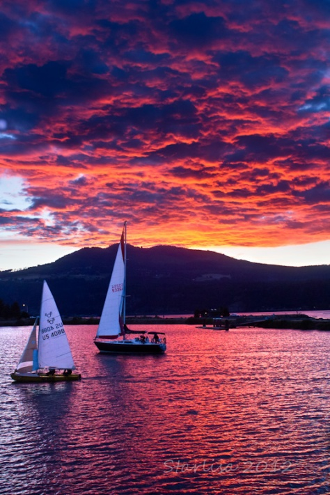 Sailboats cross paths in the Port of Hood River, during a brilliant pink to purple sunset over the Columbia River.