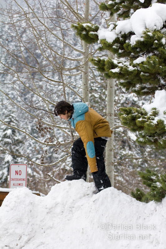 boy climbs mountain of snow