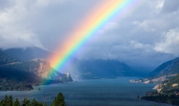 large rainbow seen over the Columbia River from White Salmon, with one end touching the stone outcropping near Hood River called Guardian of the Gorge.